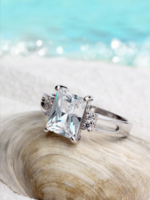 platinum diamond ring sitting on seashell with beach background